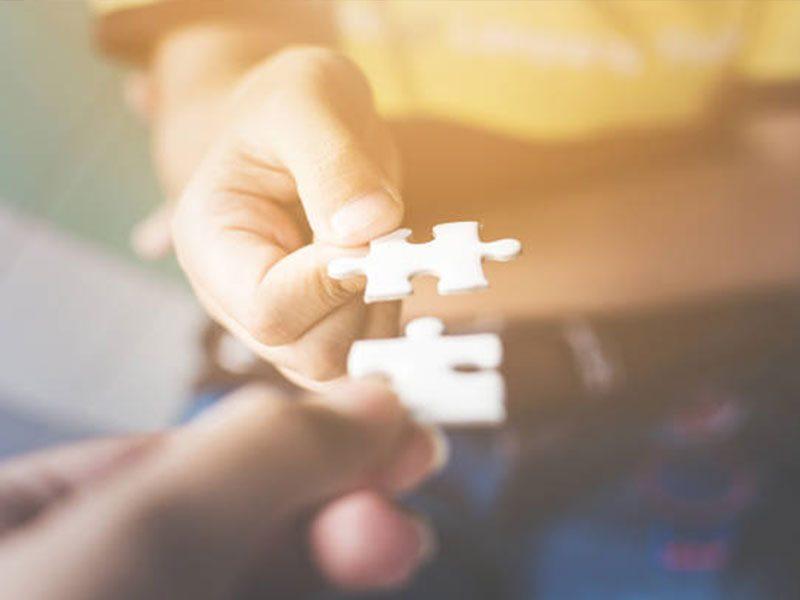 enfant et adulte tendent une pièce de puzzle